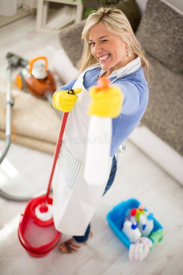 Горничная с продуктами для очищая дома в руках делает шутку стоковые фотографии rf
