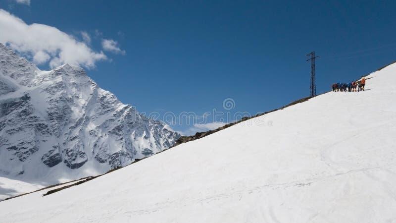 Горные пики Cheget, снег-белая панорама, туристы взбираются вверх гора Перемещение к России стоковые изображения