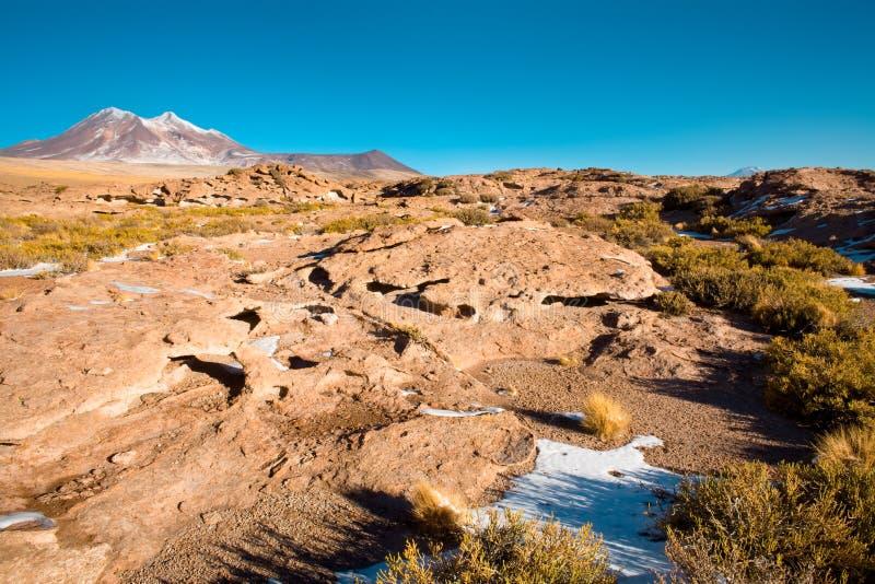 Горные породы сухой лавы, с холмом Cerro Miniques Miniques на заднем плане в Altiplano стоковое изображение