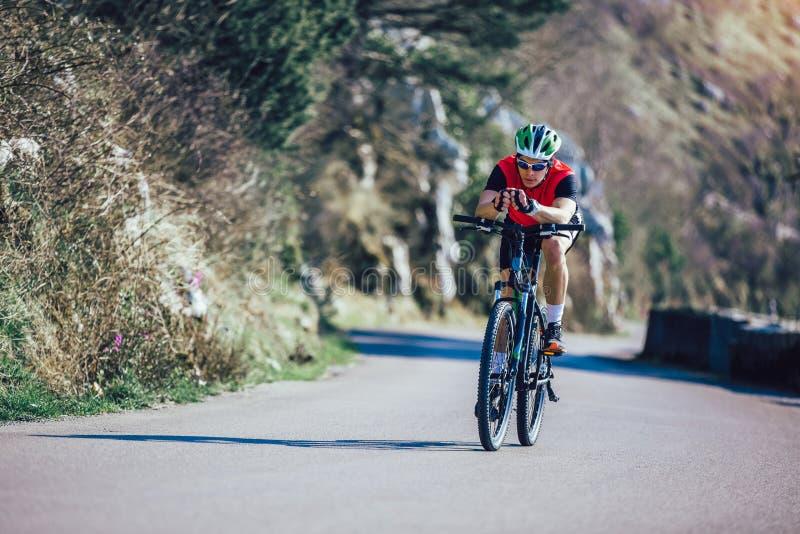 Горный велосипед езды человека на дороге стоковое фото rf