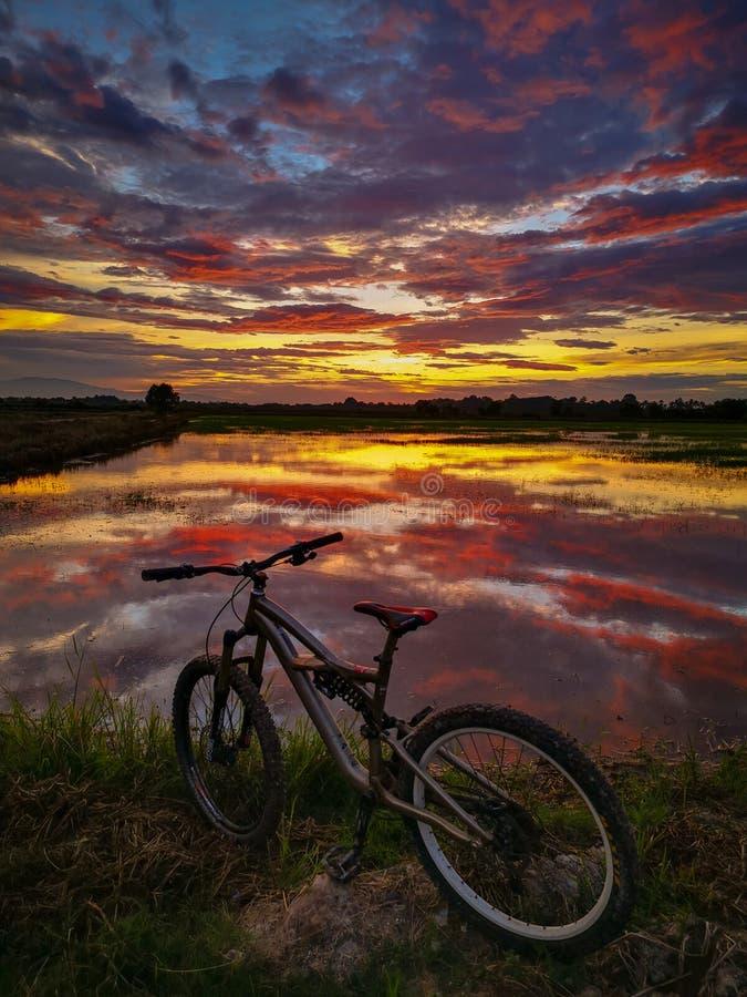 Горный велосипед и красивый заход солнца стоковое фото rf