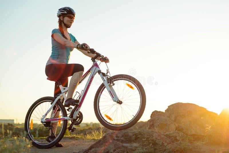 Горный велосипед катания молодой женщины на следе лета скалистом на красивом заходе солнца Перемещение, спорт и концепция приключ стоковое изображение rf