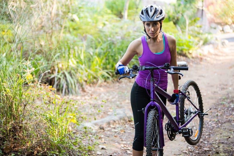 Горный велосипед нося женского велосипедиста пока идущ стоковое изображение