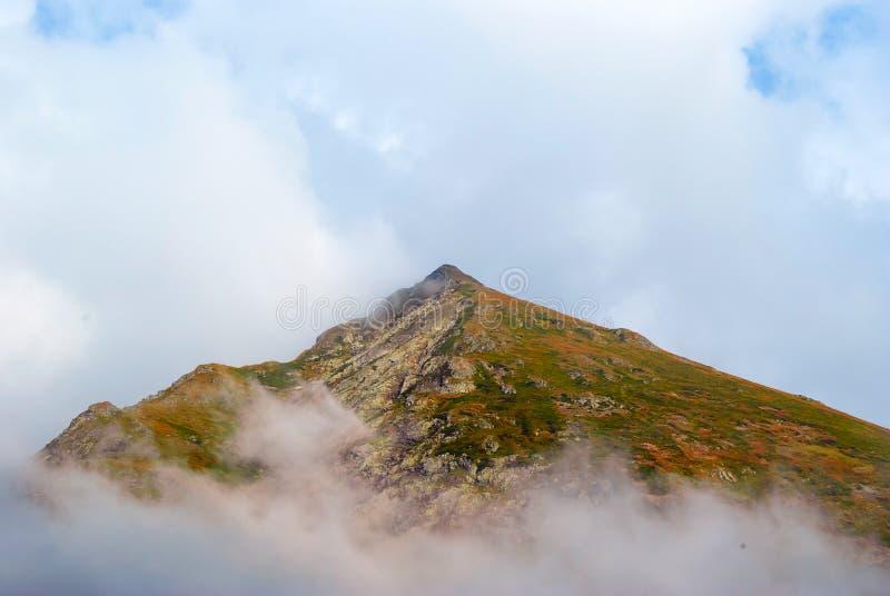 Горный пик среди облаков стоковое изображение