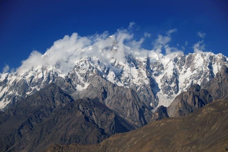Горный пик Ultar Sar за облаками стоковые фотографии rf