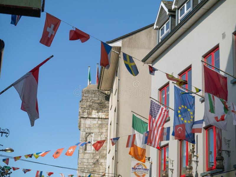 07/03/2019 городов Голуэй, Ирландия Флаги международных стран вися над улицей магазина стоковые фотографии rf