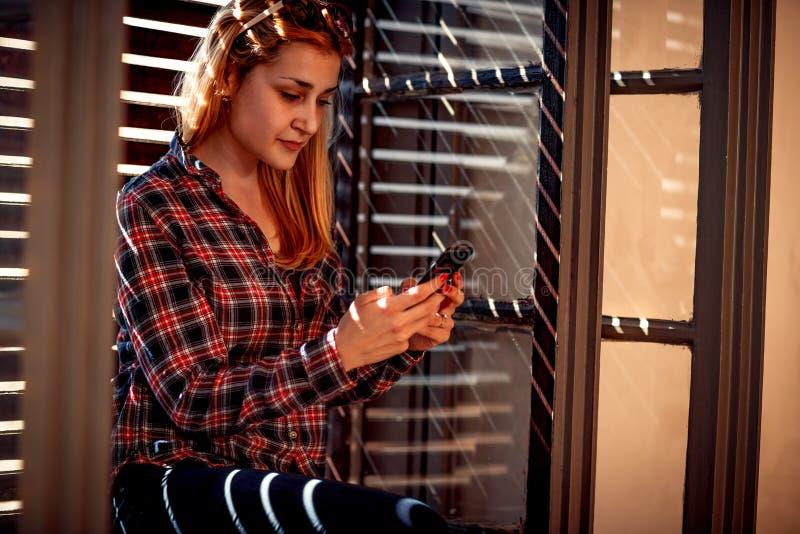 Городская девушка держа мобильный телефон и отправляя СМС послание стоковая фотография
