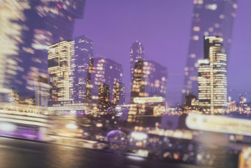 Городская еженощная абстрактная предпосылка небоскребов с вечером освещает в окнах стоковые изображения rf