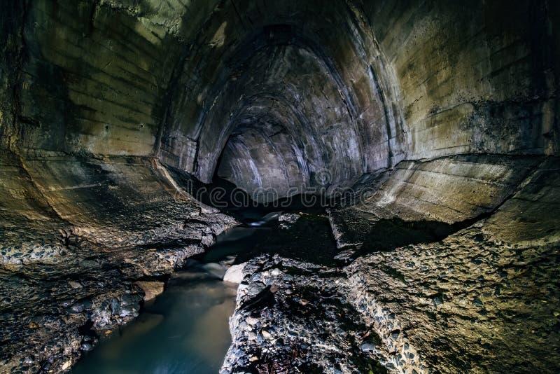 Городские нечистоты пропуская через большой oviform подземный поворачивая тоннель сточной трубы стоковое изображение