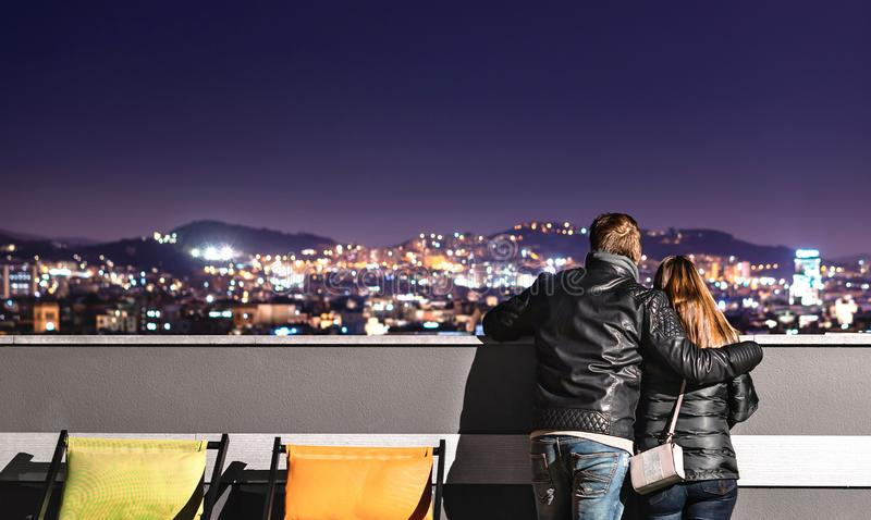 Городские пары смотря вид на город от крыши Рука удерживания парня вокруг его девушки Романтичный вечер на дата стоковое изображение