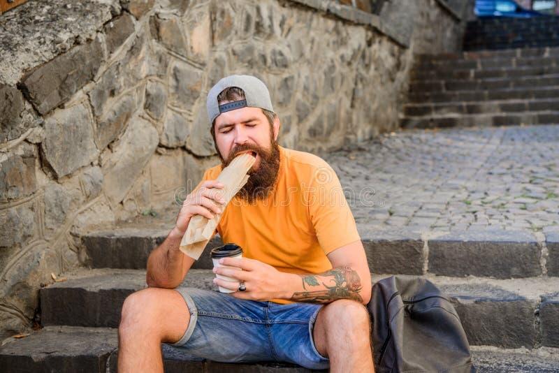 Городское питание образа жизни Беспечальный хипстер съесть высококалорийную вредную пищу пока сидите на лестницах Голодная закуск стоковое фото