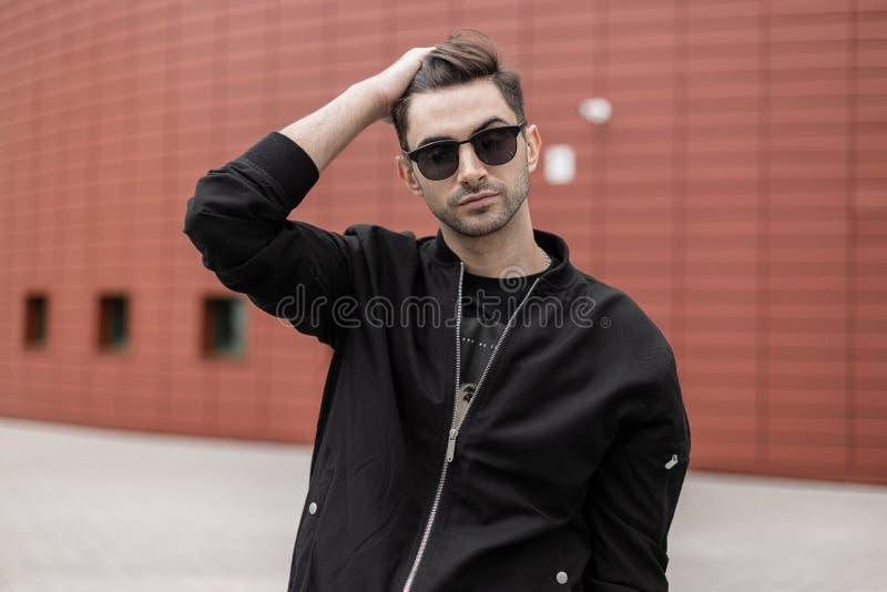 Городской американский молодой человек со стильным стилем причесок в модной черной куртке в винтажный представлять солнечных очко стоковая фотография rf