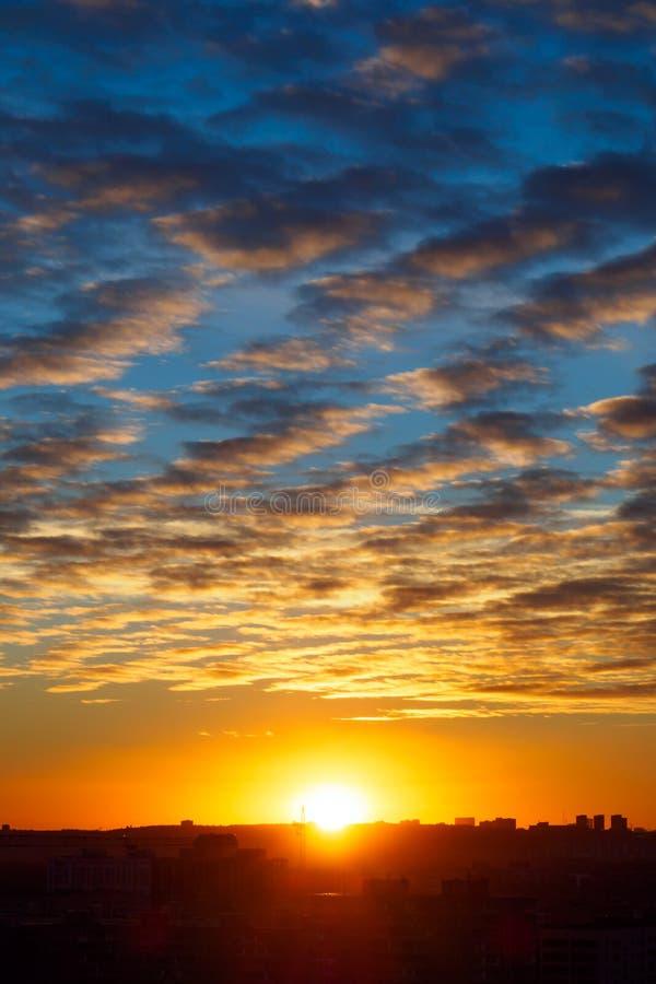 Городской ландшафт с заходом солнца, облаками цирруса и зданиями, вертикальным взглядом стоковая фотография