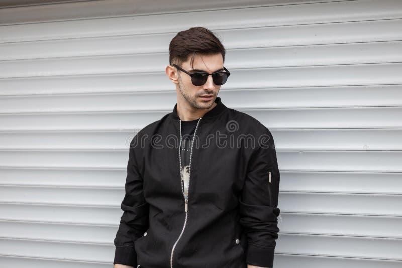 Городской молодой привлекательный человек хипстера в стильной черной куртке в ультрамодных солнечных очках с модной стойкой стиля стоковое изображение rf