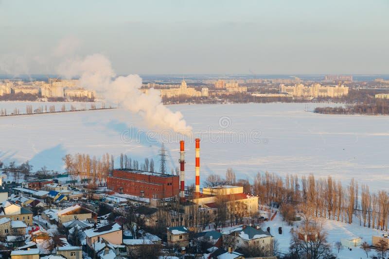 Городской пейзаж Воронежа зимы на солнечном вечере Замороженное река, куря трубы электрической станции тепловой мощности стоковое изображение