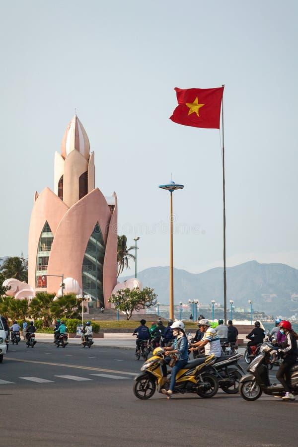 Городской пейзаж города Nha Trang с известной башней цветка лотоса и красным въетнамским флагом стоковое фото rf