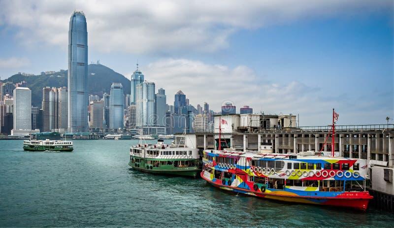 Городской пейзаж острова Гонконга от Kowloon с паромами на пристани стоковая фотография rf