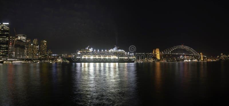 Городской пейзаж панорамы: Чудесный взгляд ночи красочных города и туристического судна около моста гавани на Сиднее, Австралии В стоковые изображения