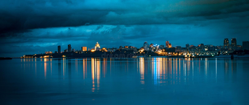 Городской пейзаж: Света города ночи на горизонте отражены в ровной воде стоковое изображение rf
