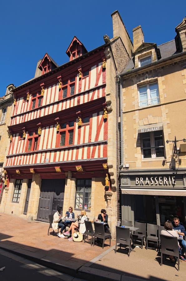 Городской пейзаж с туристами, сувенирными магазинами и кафем в средневековой деревне отдел Байё, Кальвадоса Нормандии, Франции стоковое фото