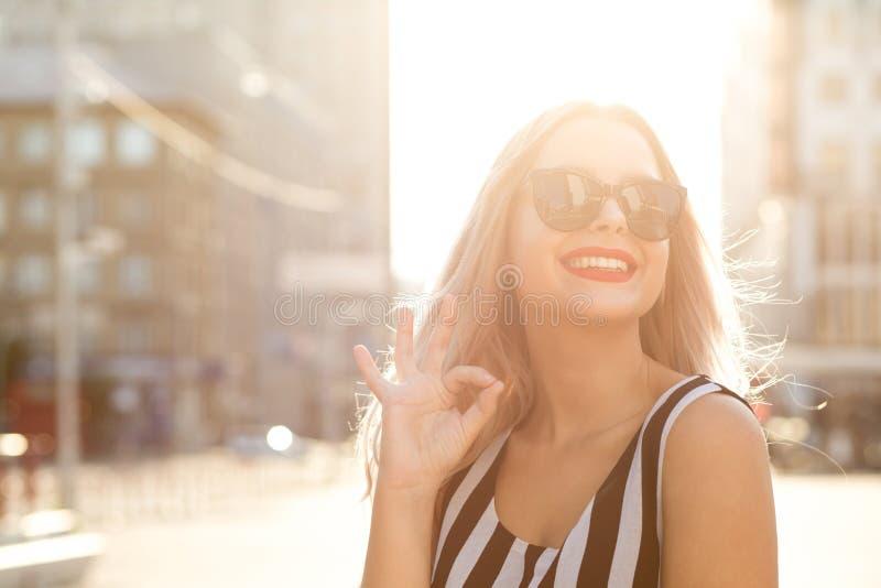 Городской портрет девушки очарования жизнерадостной в стеклах показывая одобренные ges стоковые изображения
