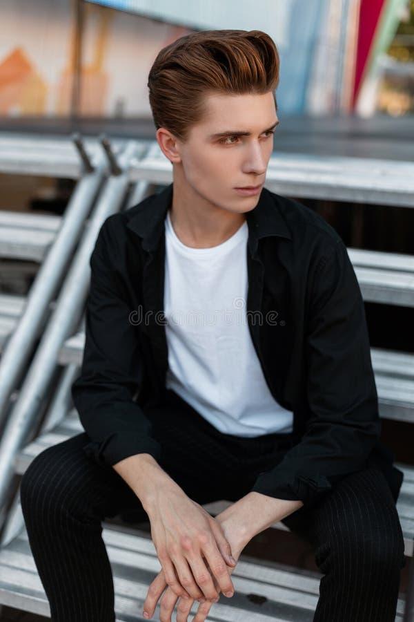 Городской привлекательный молодой человек со стильным стилем причесок в футболке в элегантной черной рубашке в ультрамодный отдых стоковые изображения rf