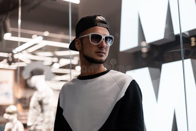 Городской хипстер молодого человека с бородой в черной бейсбольной кепке в белых стильных солнечных очках в модной фуфайке стоит стоковое фото