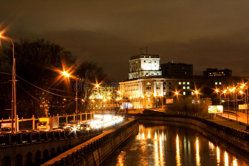 Город вечером вдоль реки стоковые изображения