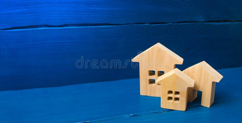 Город, поселение minimalism для представлений рынок недвижимости 3 дома на голубой предпосылке Покупка и продажа стоковая фотография rf