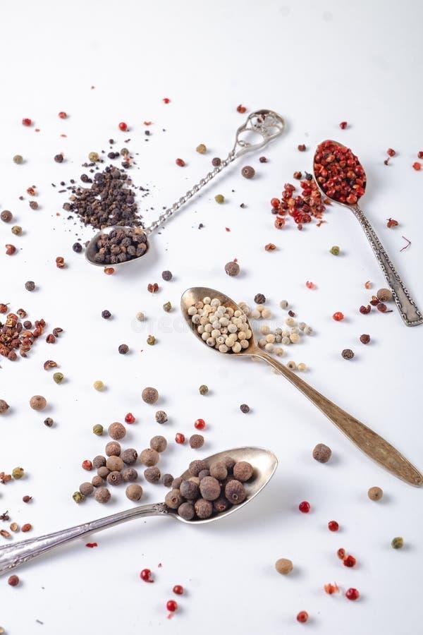 Горохи черного, красного, белого перца в ложках металла на белой предпосылке chili, паприка стоковая фотография