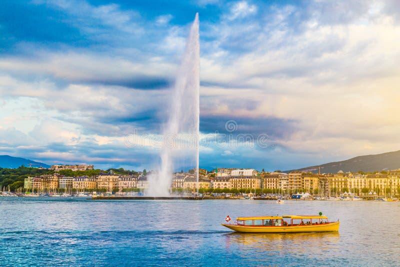 Город Женевы с известным фонтаном на заходе солнца, Швейцарией d'Eau двигателя стоковые фото