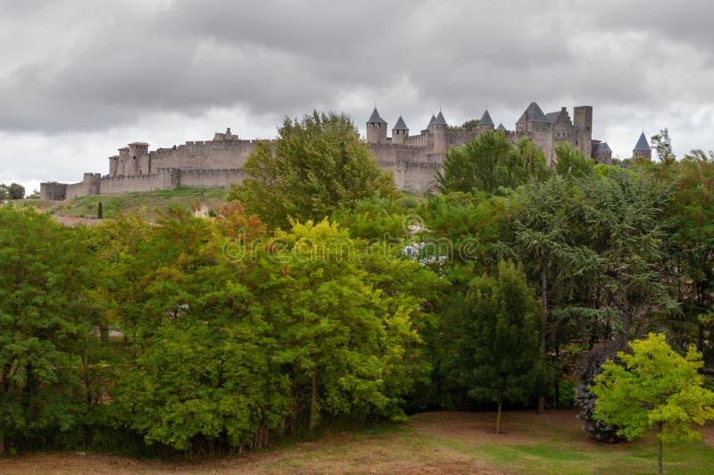 Город Каркассона старый укрепленный за древесинами с бурным небом стоковое изображение