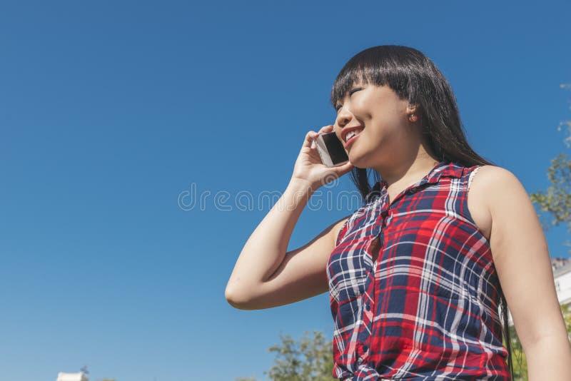Городская умная вскользь молодая азиатская женщина говоря на smartphone стоковое изображение