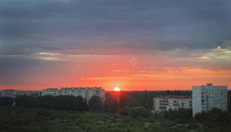 Городской ландшафт на заходе солнца с красивым оранжевым солнцем стоковая фотография rf
