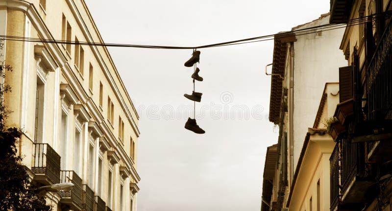 Городской ландшафт с ботинками повиснул на проводе стоковые изображения