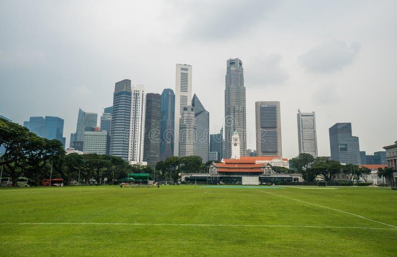 Городской пейзаж Сингапура с футбольным полем и высокими коммерчески зданиями стоковые фотографии rf