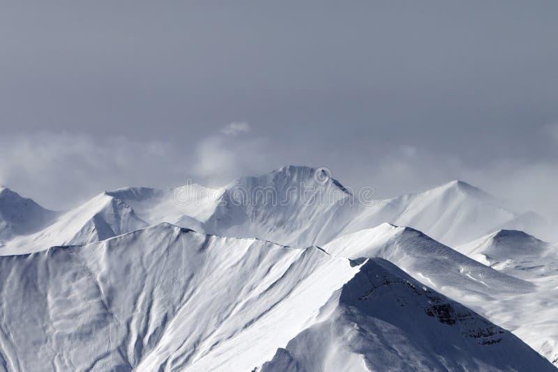 Горы зимы Snowy в помохе и облачном небе на сером дне стоковое изображение rf