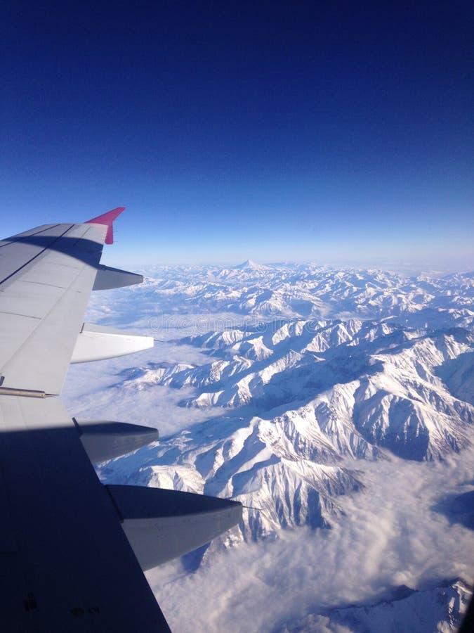 горы летания сверх Взгляд сверху из окна самолета стоковое фото