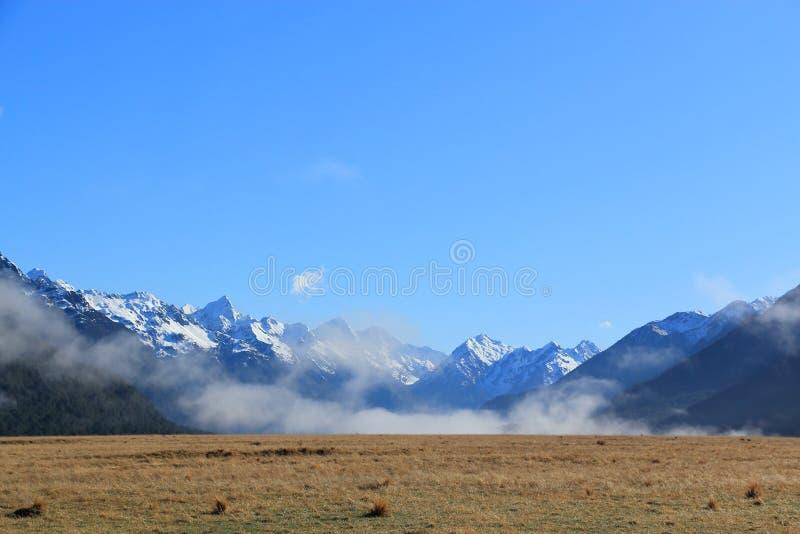 Горы покрытые снегом с голубым небом стоковые изображения rf