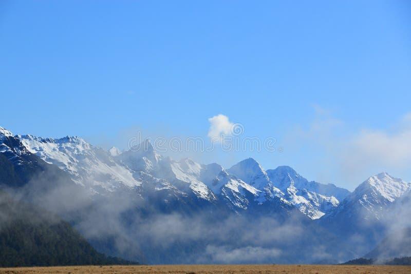 Горы покрытые снегом с голубым небом стоковое фото rf