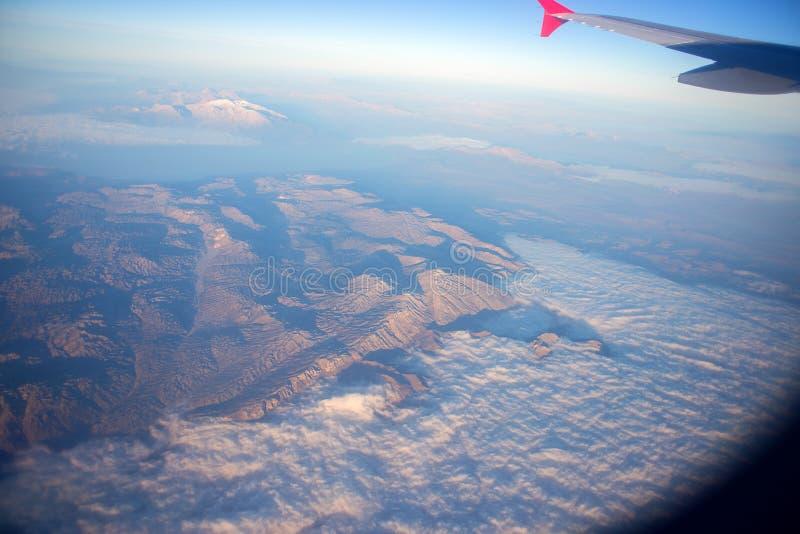 Горы покрытые с облаками, взгляд от высоты Взгляд гор из плоского окна Плоское крыло в окне стоковое изображение