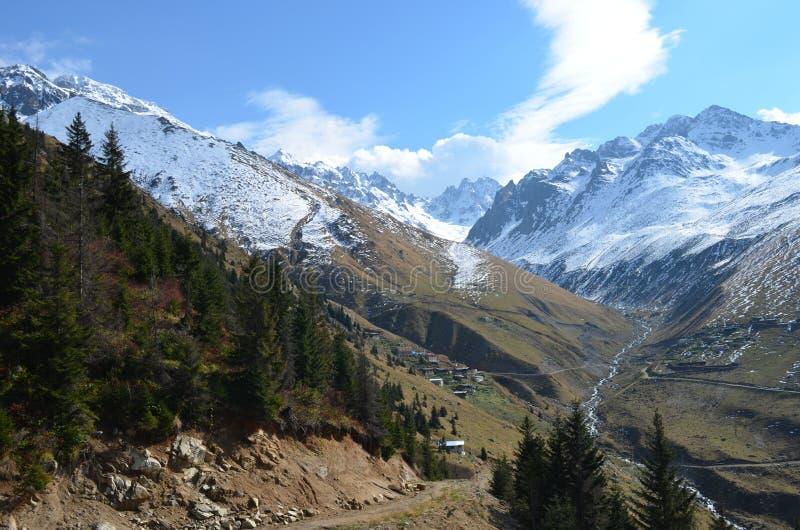 Горы предусматриванные в снеге с облаками в предпосылке стоковые фото