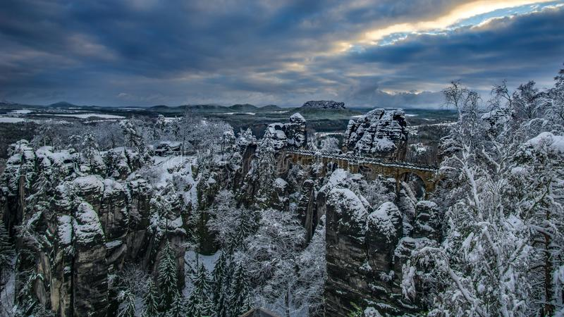 Горы с лесом на реке в зиме от моста в горах песчаника Эльбы, saxon национального парка Bastei Швейцарии, стоковая фотография