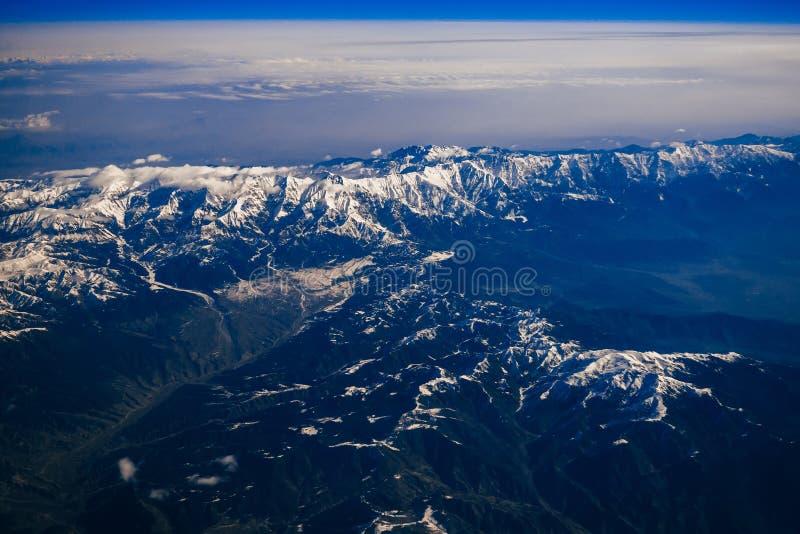 Горы с снежными пиками и небо с голубыми облаками стоковое изображение
