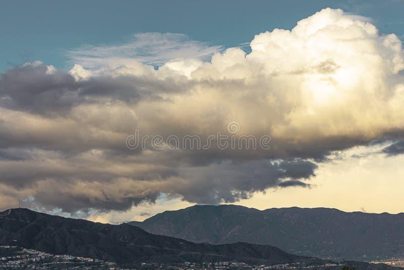 Горы с cloudscape домов с кумулюсом, облака nimbus с голубым небом стоковое фото rf