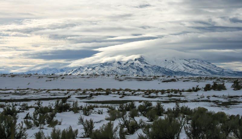 Горы Snowy при облака разделяя во время зимы бушуют стоковое фото