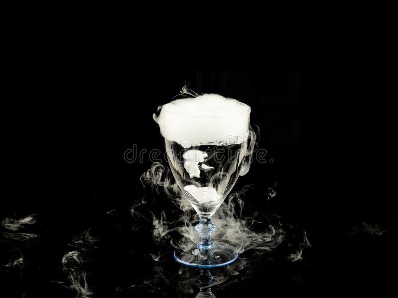 Горячая вода в бокале с дымом на черной предпосылке стоковая фотография