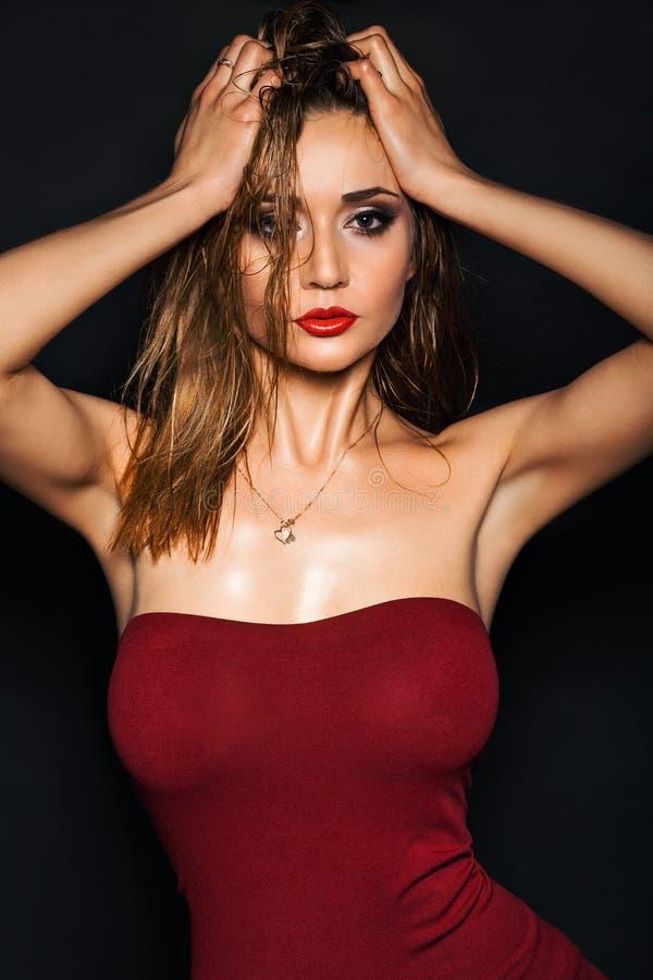 Горячая модель молодой женщины с сексуальным ярким красным составом губ, сильными бровями, чистой сияющей кожей и влажным стилем  стоковые фото