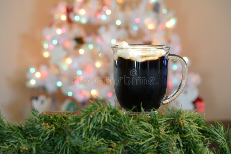 Горячая чашка какао представленная перед белой рождественской елкой с покрашенными светами стоковое фото rf