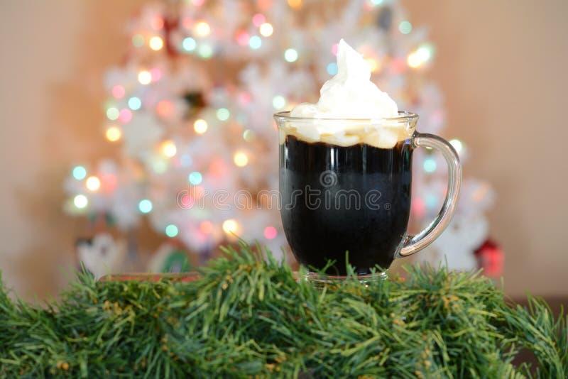 Горячая чашка какао представленная перед белой рождественской елкой с покрашенными светами стоковое изображение rf